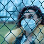 一位女性戴著醫療口罩在欄網後方試看